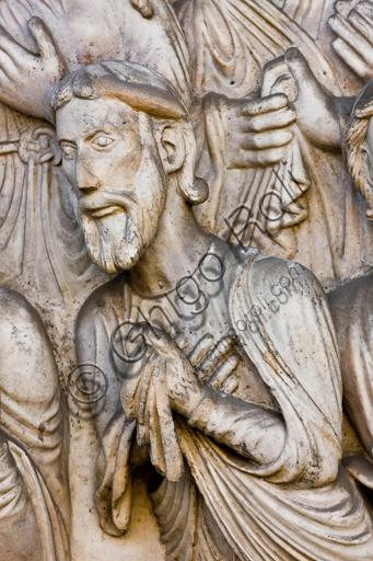 """Genova, Duomo (Cattedrale di S. Lorenzo), lato ovest, la facciata, portale maggiore: dettaglio della lunetta con """"Il martirio di S. Lorenzo"""", di Maestro della lunetta della Cattedrale di Genova, 1225 circa.Particolare con persona che assiste al martirio."""