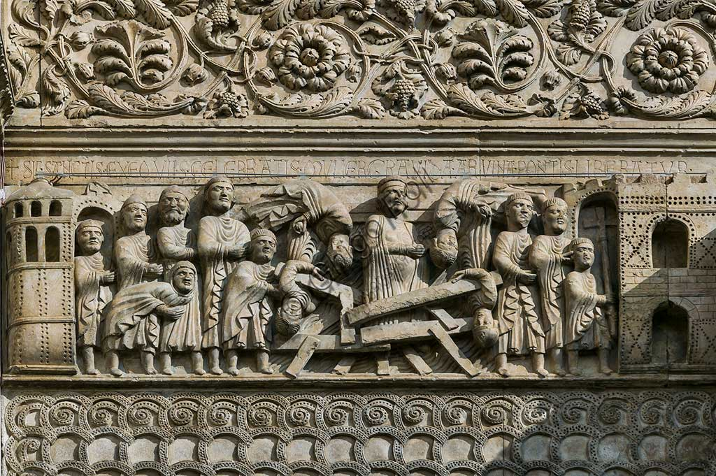 "Fidenza, Duomo (St. Donnino Cathedral), Façade: the bas-relief with Stories of San Donnino, ""The Miracle of the Pregnant Woman"", which dramatically tells the story of the collapse of an overly crowded bridge and the rescue of the pregnant woman through the intervention of the Saint. Work byBenedetto Antelami and his workshop."
