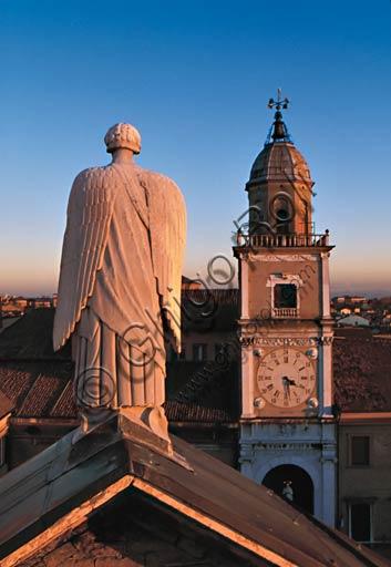 Modena: statua dell'Arcangelo Gabriele sul timpano del transetto centrale del Duomo e, sullo sfondo, la Torre Civica.