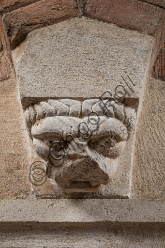 Modena, Ghirlandina Tower, Torresani Hall, east wall: a Corinthian capital with a sculpted face in the abacus protome. Campionese Masters, XII - XIII century. Detail.