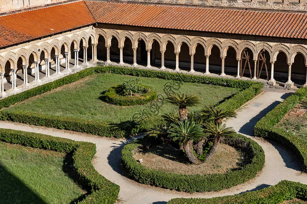 Monreale, Duomo, cloister of the Benedictine monastery: view of the cloister (XII century) with  arch colonnades and flowerbeds with palm trees.