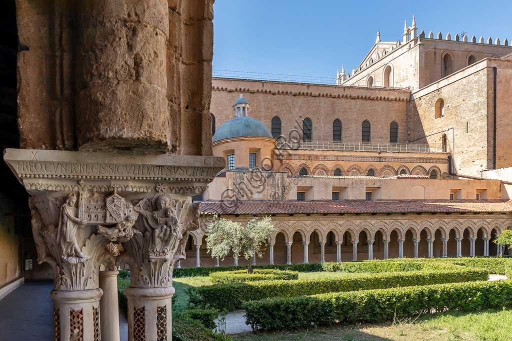 "Monreale, Duomo, the cloister of the Benedectine monastery (XII century): the Southern side of capital W8; ""William II the Emperor offering the Cathedral to the Virgin and Infant Jesus"". In the background, the Southern side of the Cathedral, the flowerbeds and an olive tree."