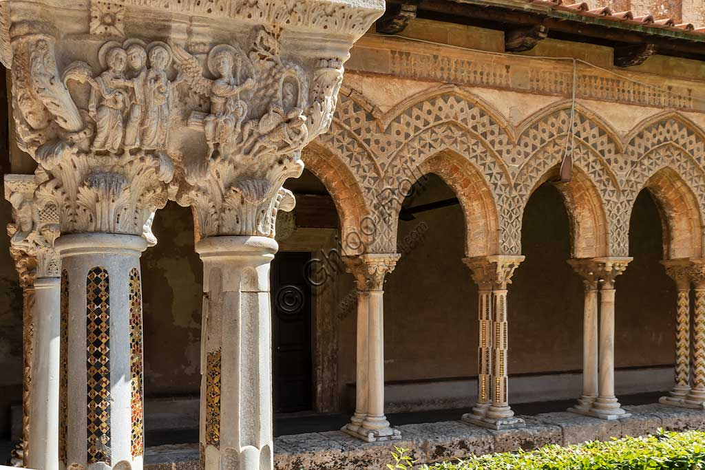 "Monreale, Duomo: view of the cloister, XII century. In the foreground, the Northern side of capital E24 (""The Pious Women at the sepulchre - The angel shows the empty sepulchre"")."