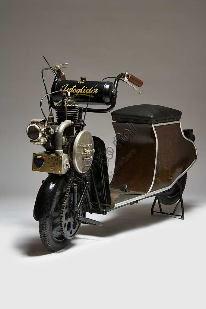 Moto d'epoca Autoglider. Scooter.Marca: Townsend Engineering Companymodello: Autoglider nazione: Regno Unito - Birminghamanno: 1919condizioni: restauratocilindrata: 300motore: monocilindrico a due tempi cambio: Dando seguito al grande senso di libertà che seguì la fine della Grande Guerra, e alla conseguente voglia di spostarsi liberamente, il 1919 segnò in Gran Bretagna una stagione di grande successo popolare per gli scooter e le moto in genere.L' Autoglider fu costruito a Birmingham da Charles Ralph Townsend dapprima nel Model A, senza sella. Ma questo modello che obbligava alla posizione in piedi, non ebbe successo. Poi nei successivi modelli con una piccola e curvilinea carrozzeria in legno compensato che sorreggeva la sella fungendo anche da vano portaoggetti come negli scooter attuali. Poteva montare un motore Villiers di 269 cc, oppure, come in questo caso, un motore Union di 300 cc.Conobbe una certa diffusione e lo si riconosce spesso in molte fotografie dell'epoca.