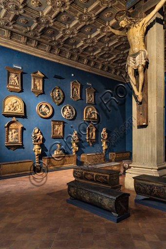 Museum Stefano Bardini: the room of the reliefs of Madonna with Infant Jesus and, on the right, the Crucifix in polychrome wood, XV century.