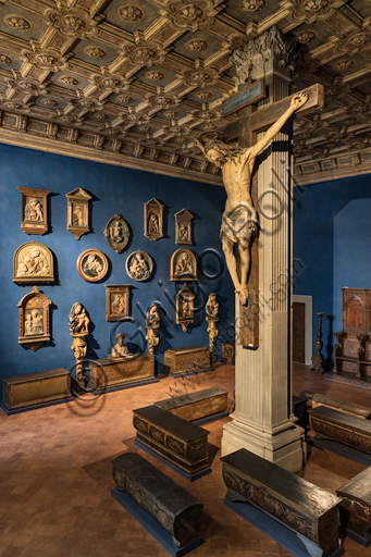 Museum Stefano Bardini: the room of the reliefs of Madonna with Infant Jesus and, at the centre, the Crucifix in polychrome wood, XV century.