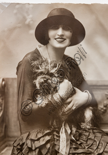 """Nella Regini with a dog in her arms"", sepia carbon print by Marcello Dudovich, 1926."