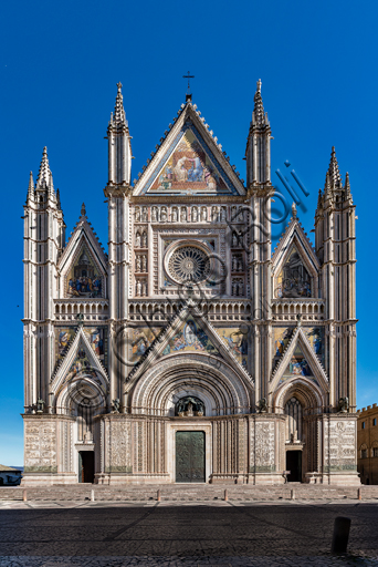 Orvieto, Basilica Cattedrale di Santa Maria Assunta (o Duomo): la facciata, iniziata alla fine del XIII secolo. Il disegno tricuspidale venne progettato da Lorenzo Maitani ed eseguito dallo stesso Maitani con l'aiuto di maestranze pisane e senesi (1320 -30). L'esecuzione fu continuata da Andrea Pisano (1347) e dall'Orcagna (1359) a cui si deve il rosone.