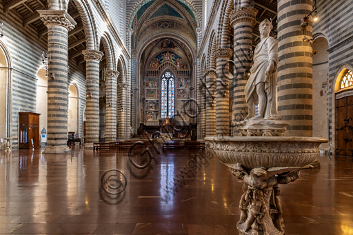 Orvieto,  Basilica Cathedral of Santa Maria Assunta (or Duomo): the interior  (XIII - XIV century). In the foreground, the holy water font by Camillo Cardinali.