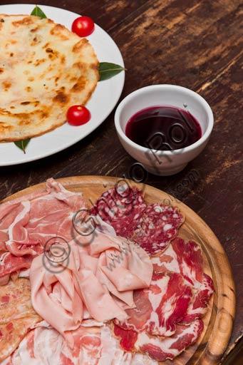 Osteria La Carrozza:  tagliere di salumi tipici piacentini, piatto con una bortellina (una sorta di crepe senza uova) e vino rosso dei Colli piacentini.