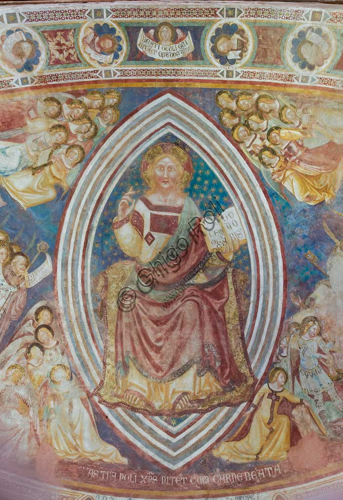 """Codigoro, the Pomposa Abbey, interior of the Basilica of Santa Maria, apse: fourteenth-century frescoes by Vitale da Bologna, depicting Christ in majesty with angels and saints. Detail of blessing Christ in majesty within the almond and holding the book with the words """"pacem meam do vobis"""" in his left hand."""