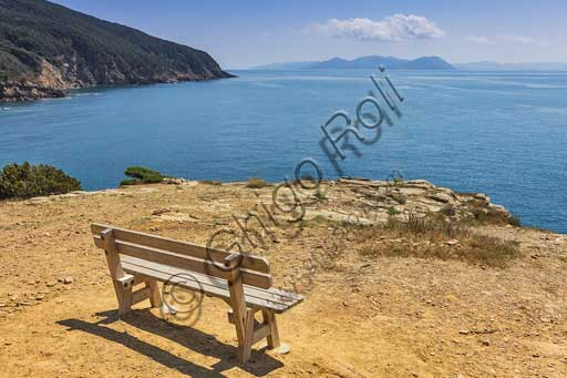 Bench on the coast of  the Piombino Promontory in the vicinity of Buca delle Fate (Fairies Cove). In the background, the Elba Island.