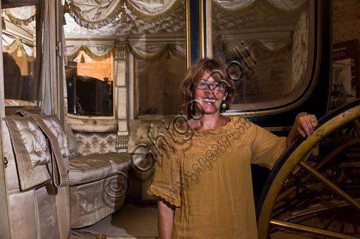 Piacenza, Palazzo Farnese, Musei Civici: il direttore dei Musei Civici Farnesiani, Antonella Gigli, in una delle sale del Museo delle Carrozze. Il direttore è davanti a una delle carrozze date in prestito illimitato dal Presidente della Repubblica Italiana.