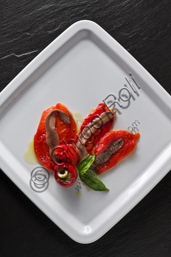 A plate of anchovies and peppers, with basil.