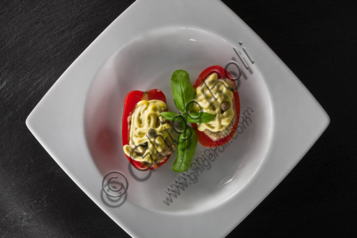 A dish of filled tomatoes covered with mayonnaise and basil leaves.