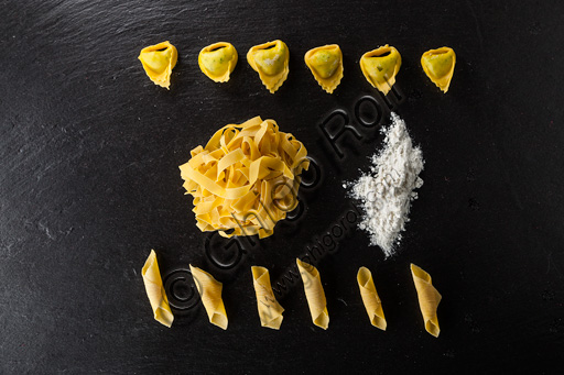 A plate of raw tagliatelle and garganelli (kind of typical Italian pasta), tortelloni and flour.