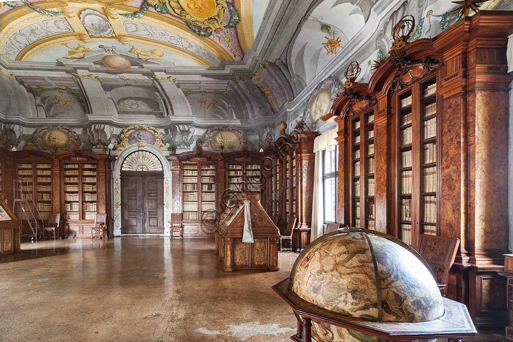 Pontificia Biblioteca Antoniana: veduta del Salone con mappamondo, librerie  e mobili contenenti corali miniati.