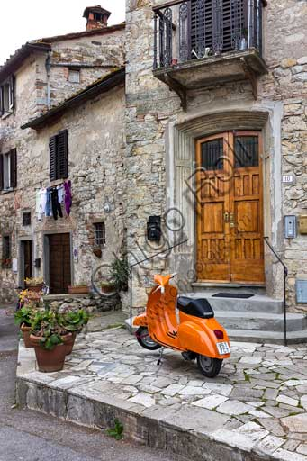 Radda in Chianti: partial view of the village with a scooter Vespa.