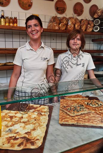 Recco, Moltedo traditional bakery: Luisa Moltedo is cutting a piece of focaccia bread.