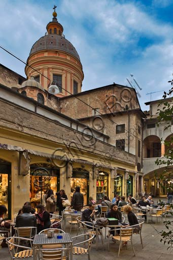 Reggio Emilia, Prampolini Square: night view of the Broletto. People sitting at bar tables.