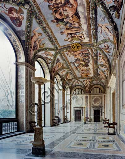 Rome, Villa Farnesina: view of the Loggia of Cupid and Psyche.The Loggia takes its name from the decoration frescoed on the vault by Raphael and his workshop in 1517-18. The frescos represent episodes from the fable of Psyche, narrated in Apuleiu's Golden Ass, which had already been used in the fifteenth century for nuptial imagery.To give the space a festive and theatrical feel to it, Raphael also transformed the vault of the Loggia into a pergola, adorned with magnificent hanging festoons, as though the greenery of the gardens had invaded the Villa itself. In the centre he designed two fictive tapestries which depict the concluding scenes: the splendid Council of the Gods, where the unjustly persecuted girl is finally received by the gods with divine complacence, and the Marriage of Cupid and Psyche, the symbolic culmination of the entire cycle.However, although the general layout of the cycle and planning of the individual scenes and figures are attributed to the intuitive genius of Raphael (proven by a number of autographic sketches), the actual completion of the designs into frescos was carried out by his numerous workshop assistants, including Giovanni Francesco Penni, Giulio Romano and Giovanni da Udine. The latter, in particular, was the creator of the exuberant triumphal festoons.