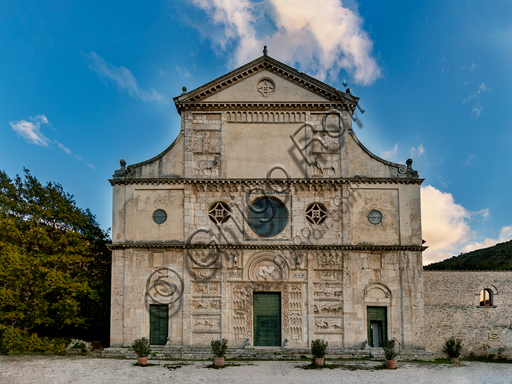 Spoleto, St. Peter's Church: the façade. It is characterized by Romanesque reliefs (XII century). It is divided into three parts: the upper one is surmounted by a tympanum with the statue of Saint Peter. The space that was probably destined to  a mosaic is flanked by panels with reliefs of St. Peter, St. Andrew and two bulls. The median part is characterized by three oculi. The central one is framed by a cosmatesque decoration and surrounded by symbols of the Evangelists. In the lower part there are three portals bordered by animals. The side portals are surmounted by reliefs. in the one on the right there is a holy bishop, in the one on the left there is St Michael struggling against the dragon.