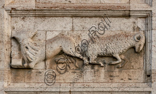 """Spoleto, St. Peter's Church, the façade ( It is characterized by Romanesque reliefs (XII century), detail of one of the five bas-reliefs to the right of the main portal: """"Fable of the student wolf and the ram (probable satire of the monastic life)""""."""