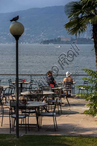 Stresa: the lakefront with two tourists sitting at a table, and a pigeon on a lamppost. In the background, Isola Madre.