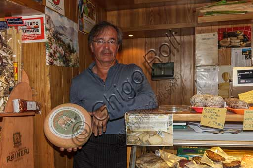 Stresa, Latteria Coppola: the owner shows a wheel of Mottarone cheese