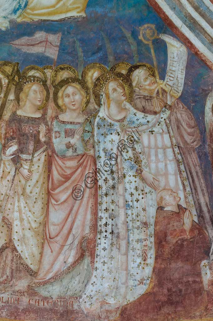 "Codigoro, the Pomposa Abbey, interior of the Basilica of Santa Maria, apse: fourteenth-century frescoes by Vitale da Bologna. Detail of the Virgin Mary, depicted in a precious gold embroidered dress, while presenting the patron abbot Andrea. She holds the cartouche with the inscription ""tuam fili clementiam"" in her left hand. The latin text is a recommendation for the community of Pomposa and for humanity. Next to her, the holy Benedictine is Guido, while in the foreground there are the saints Caterina, Orsola, Elena and Maddalena."