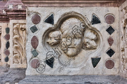 """Genova, Duomo (Cattedrale di S. Lorenzo), lato ovest, la facciata, il portale maggiore: """"Volto e due cani"""", di Maestro dell'Arca del Battista (1225 circa), formella figurata della decorazione del basamento."""