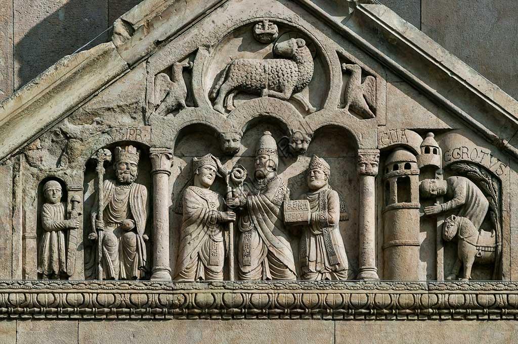 """Fidenza, Duomo (Cattedrale di S. Donnino), Facciata, frontone del protiro del portale di sinistra. Da sinistra a destra: """"L'imperatore Carlo Magno, con un armigero alla sua destra""""; """"Papa Adriano II che porge all'arciprete di San Donnino la mitria e il pastorale"""" (simboli della dignità episcopale);""""Il miracolo dell'ammalato guarito"""", (miracolo compiuto da San Donnino).Opera di Benedetto Antelami e bottega."""
