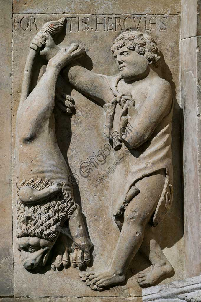 """Fidenza, Duomo (St. Donnino Cathedral), Façade, the right portal, inside the protiro: """"Hercules shows the Nemean lion he killed"""". Bas-relief by Benedetto Antelami and workshop."""