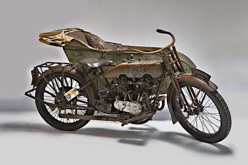 """Moto d'epoca Harley-Davidson T - SideMarca: Harley-Davidsonmodello: T Sidenazione: U.S.A. - Milwaukeeanno: 1917condizioni: conservatacilindrata: 1000 (alesaggio e corsa 84,1 x 88,9)motore: bicilindrico a V di 45°cambio: a tre rapportiFondata nel 1903 la H-D ha accompagnato tutta la storia degli Stati Uniti fino ad oggi, dalle prime moto militari usate nelle schermaglie di confine contro Pancho Villa, alle grandi forniture per l'esercito che nel 1917 era entrato in guerra sul fronte europeo, dai mezzi da lavoro (i """"tricicli"""" dei lattai e dei postini americani) alle grandi bicilindriche della polizia.. Già nel '20 era il primo produttore di motociclette al mondo.Questo elegante sidecar del 1917, integralmente conservato e perfettamente funzionante, mostra già il bicilindrico a V che caratterizza ancor oggi la produzione della Harley. Ha distribuzione a valvole contrapposte (scarico laterale, aspirazione in testa)."""
