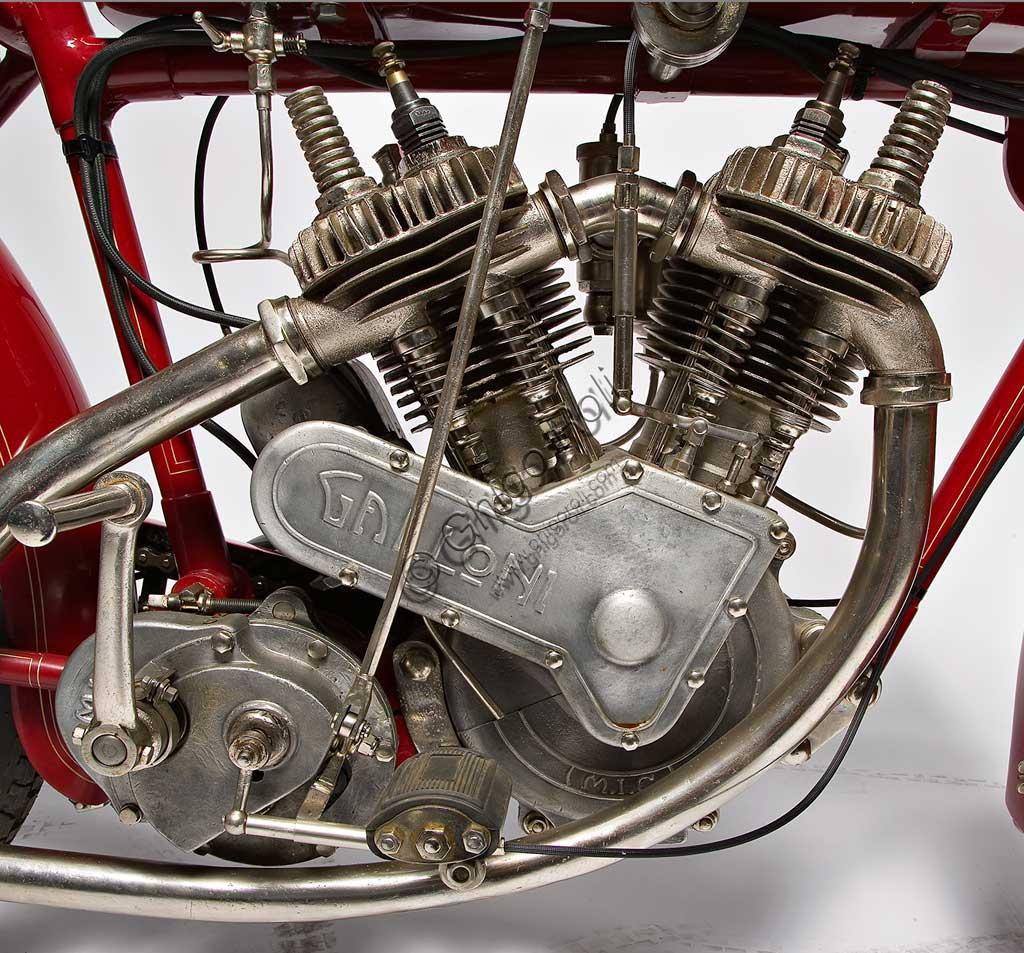 Moto d'epoca Galloni 750 SS. Motore.fabbrica: MG - Moto Gallonimodello: 750 SS fabbricata in: Italia - Borgomaneroanno di costruzione: 1920-21condizioni: restauratacilindrata: 744 cc (alesaggio e corsa: 76 x 82)motore: bicilindrico a V, a valvole lateralicambio:a mano a tre rapportiAlberto Galloni, titolare della MG di Borgomanero, costruisce la sua prima moto da corsa nel 1919. In sella a questa bicilindrica il pilota Miro Maffeis si aggiudica alcuni record mondiali. L'anno successivo inizia la produzione di serie con una due tempi ed una 500 quattro tempi bicilindrica. La fabbrica rimarrà attiva fino al 1932, creando una decina di modelli, alcuni dei quali  raccolsero diversi successi in campo sportivo con i piloti Augusto Rava e Alfredo Panella. L'esemplare qui mostrato divide con un'altra moto simile di 500 cc, l'onore di essere l'unica superstite nota di tutta la produzione. Elegante nelle forme e nelle soluzioni tecniche, ha cilindri e teste nichelati, tappi delle teste interamente alettati, serbatoio a due scomparti con dosatore regolabile, forcella elastica brevettata a due molle in compressione. Monta un freno a tamburo sulla ruota posteriore.