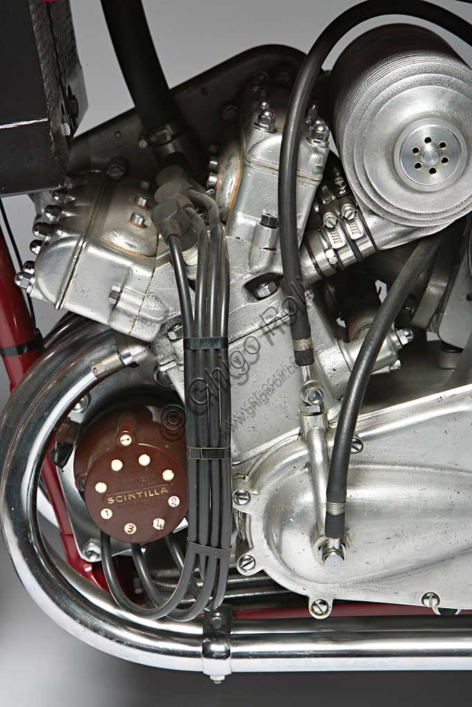 Moto d'epoca Benelli 250 Corsa 4 Cilindri con Compressore. Motore.Marca: Benellimodello: 250 Corsa 4 Cilindri con Compressorenazione: Italia - Pesaroanno: 1942condizioni: restauratacilindrata: 248,2 (alesaggio e corsa 41 x 47)motore: quattro cilindri con compressorecambio: in blocco a quattro rapportiAnche la forma del manubrio, che ricorda le corna di un toro, sembra voler sottolineare la potenza, realmente mostruosa per i tempi, di questa Benelli da competizione. Grazie a un compressore Cozette, azionato da ingranaggi innestati sul cambio, la 250 quattro cilindri sprigionava 55,2 Hp a 13.000 giri e, a dispetto della cilindrata di soli 250 cc, raggiungeva i 230 km/h. Concepita nel '39 fu prodotta in pochissimi esemplari di cui questo sembra l'unico superstite. A causa della guerra non partecipò a nessuna competizione e rimane uno degli esempi più alti delle capacità tecniche dell'industria motociclistica di quell'epoca.