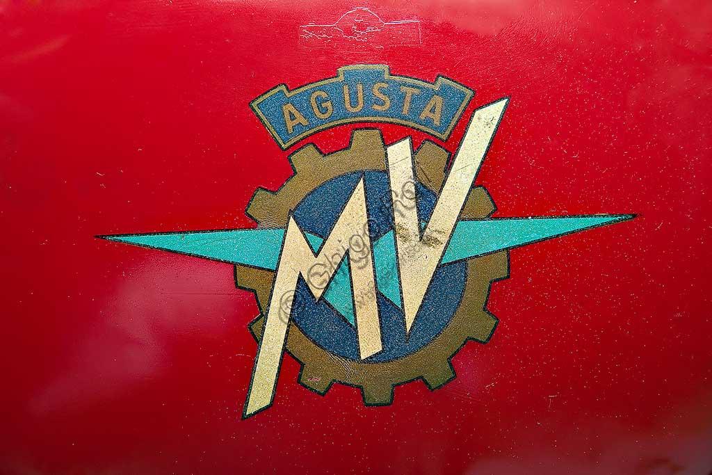 Moto d'epoca MV Agusta 125 Monoalbero Corsa. Marchio.Marca: MV Agustamodello: 125 Monoalbero Corsanazione: Italia - Schiranna (VA)anno: 1954condizioni: conservatacilindrata: 123,5 (alesaggio e corsa 53 x 56)motore: monocilindrico, albero a cammes in testacambio: a quattro rapportiLa storica azienda fondata nel 1907 dal Conte Giovanni Agusta, nota per la produzione aeronautica, iniziò a produrre motociclette con il figlio Domenico solo nel '46, con il nome Meccanica Verghera (MV). Dopo le prime 98, nelle versioni Turismo e Sport, costruisce moto sempre più orientate verso le competizioni; questo esemplare, che toccava i 150 km/h, ne è una delle prime testimonianze.E' appena il caso di ricordare che, la MV con  75 campionati del mondo e 270 Gran Premi vinti, è la marca più vittoriosa della storia del motociclismo. Un record nei record: con Giacomo Agostini, vinse ininterrottamente il campionato del mondo dal 1967 al 1973 sia nella classe 350 che nella 500.