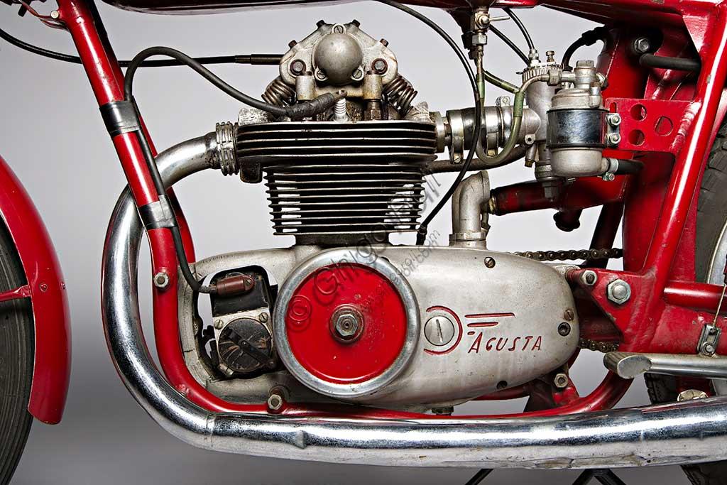 Moto d'epoca MV Agusta 125 Monoalbero Corsa. Motore.Marca: MV Agustamodello: 125 Monoalbero Corsanazione: Italia - Schiranna (VA)anno: 1954condizioni: conservatacilindrata: 123,5 (alesaggio e corsa 53 x 56)motore: monocilindrico, albero a cammes in testacambio: a quattro rapportiLa storica azienda fondata nel 1907 dal Conte Giovanni Agusta, nota per la produzione aeronautica, iniziò a produrre motociclette con il figlio Domenico solo nel '46, con il nome Meccanica Verghera (MV). Dopo le prime 98, nelle versioni Turismo e Sport, costruisce moto sempre più orientate verso le competizioni; questo esemplare, che toccava i 150 km/h, ne è una delle prime testimonianze.E' appena il caso di ricordare che, la MV con  75 campionati del mondo e 270 Gran Premi vinti, è la marca più vittoriosa della storia del motociclismo. Un record nei record: con Giacomo Agostini, vinse ininterrottamente il campionato del mondo dal 1967 al 1973 sia nella classe 350 che nella 500.