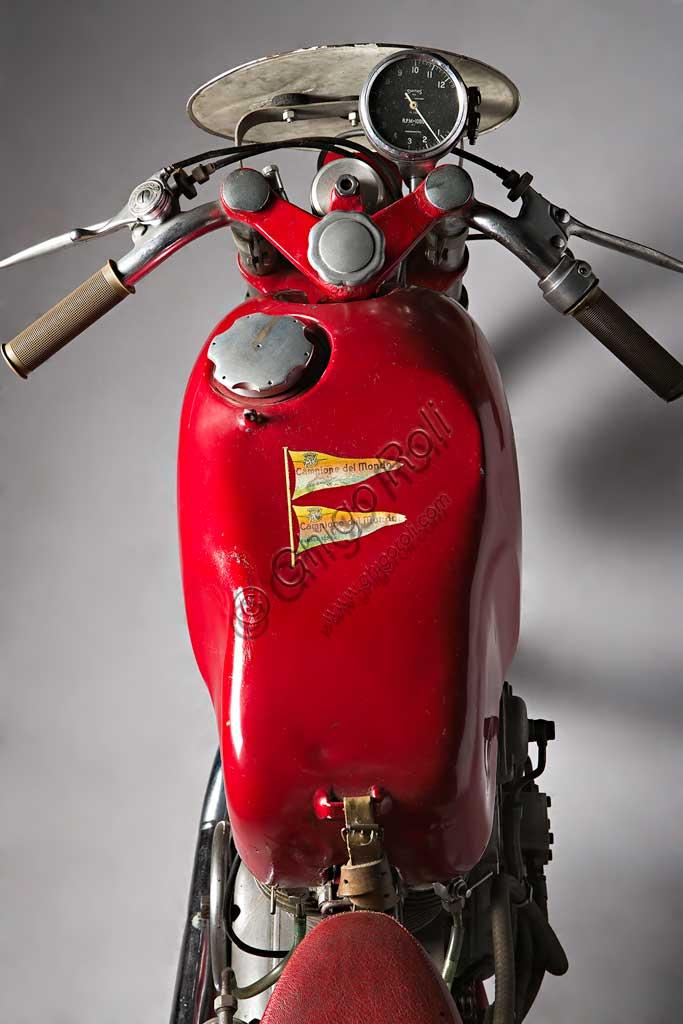 Moto d'epoca MV Agusta 125 Monoalbero CorsaMarca: MV Agustamodello: 125 Monoalbero Corsanazione: Italia - Schiranna (VA)anno: 1954condizioni: conservatacilindrata: 123,5 (alesaggio e corsa 53 x 56)motore: monocilindrico, albero a cammes in testacambio: a quattro rapportiLa storica azienda fondata nel 1907 dal Conte Giovanni Agusta, nota per la produzione aeronautica, iniziò a produrre motociclette con il figlio Domenico solo nel '46, con il nome Meccanica Verghera (MV). Dopo le prime 98, nelle versioni Turismo e Sport, costruisce moto sempre più orientate verso le competizioni; questo esemplare, che toccava i 150 km/h, ne è una delle prime testimonianze.E' appena il caso di ricordare che, la MV con  75 campionati del mondo e 270 Gran Premi vinti, è la marca più vittoriosa della storia del motociclismo. Un record nei record: con Giacomo Agostini, vinse ininterrottamente il campionato del mondo dal 1967 al 1973 sia nella classe 350 che nella 500.