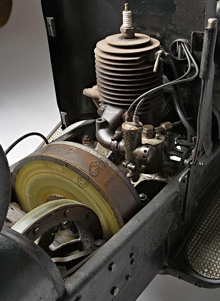 Moto d'epoca NER-A-CAR Model A. Scooter.Marca: Simplex Co. / Neracar Corp.modello: Model Anazione: U.K. - Sheffield / U.S.A. - Syracuse N.Y.  anno: 1923condizioni: restauratacilindrata: 221 (13,5 cubic inch)motore: monocilindrico a due tempicambio: trasmissione continua con variatore a volano comandato da levaGiocando sul proprio nome Carl A. Neracher battezzò Ner-A-Car questa sua creatura unica che stava a metà strada tra una moto e uno scooter e, per la sua comodità, doveva essere near a car, quasi un'automibile. Prodotta a Sheffield per l'Europa (come nel caso di questo esemplare), e a Syracuse negli States, la Ner-A-Car ha una scocca a tunnel in lamiera stampata di tipo automobilistico, molto bassa, che consente anche alle donne di guidarla facilmente e la rende molto manovrabile. Ha caratteristiche ciclistiche e meccaniche assolutamente uniche: lo sterzo è indiretto a giunto sferico collocato al centro del mozzo e comandato da tiranti;  la trasmissione è continua con variatore a volano e disco perpendicolare rivestito di materiale d'aderenza,  il comando a leva lo trasla sul volano variando, con la circonferenza, i giri. Il giornalista di Motorcycle che la recensì all'epoca, scrisse che andava molto bene ma che servivano tre mani per guidarla.