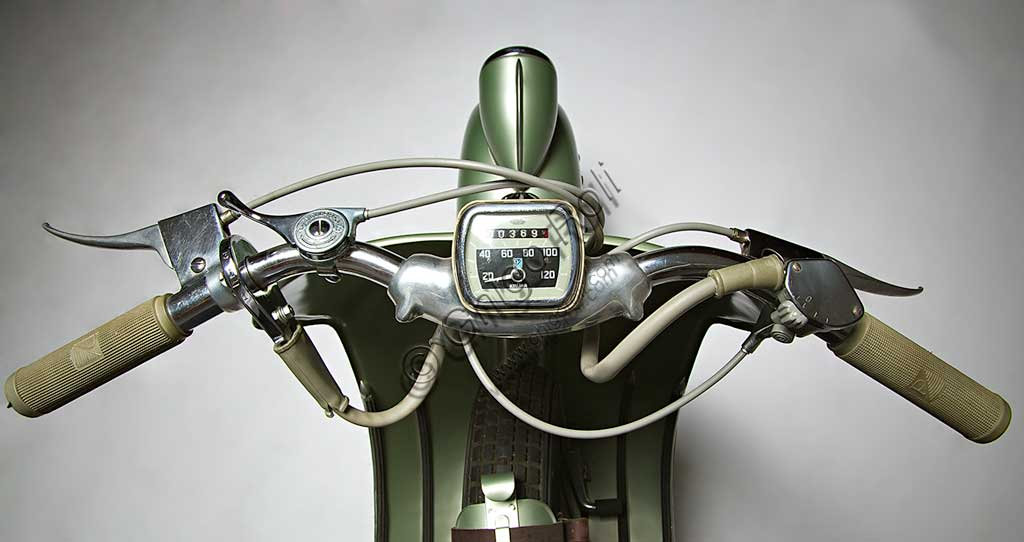 """Moto d'epoca Vespa Sei Giorni. Scooter.Marca: Piaggiomodello: Vespa """"Sei Giorni""""nazione: Italia - Genova - Pontederaanno: 1951condizioni: restauratacilindrata: 124,2motore: monocilindrico a due tempicambio: al manubrio a tre rapportiLa Vespa, che apparve per la prima volta nel 1946, è in produzione ancor oggi ed è il motoveicolo più longevo della storia. Ne sono stati prodotti oltre 16 milioni di esemplari in 140 modelli. Venne concepita già durante la guerra e, dopo un primo prototipo denominato """"Paperino"""", non particolarmente riuscito, Enrico Piaggio ne affidò il progetto a Corradino d'Ascanio, ingegnere aeronautico. Le soluzioni anticonformiste e geniali da lui adottate, oltre al grande bisogno di veicoli a basso costo che aveva l'Italia nel dopoguerra, ne decretarono un progressivo crescente successo, fino a farne, anche attraverso l'immagine che il cinema di quegli anni ne diffondeva, uno dei simboli dell'Italia. La """"Sei Giorni"""" di queste pagine è uno dei modelli più rari.  Concepita per le corse, vinse nove medaglie d'oro all'olimpiade motociclistica del 1951, la """"Sei Giorni Internazionale"""" di Varese."""