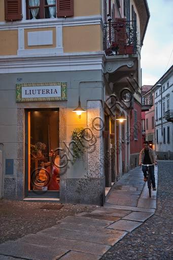 Cremona, bottega di liutaio e ragazzo in bicicletta.