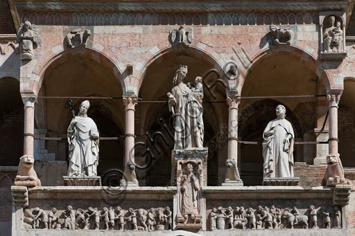 Cremona, Duomo (Cathedral), facade, loggia over the Portal: Madonna with Infant Jesus between Saint Omobono e Imerio Bishop; marble frieze representing the months (1120-1230). The statue under the Virgin Mary represents Bishop Sicardo.