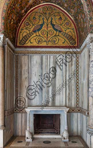 Palermo, The Royal Palace or Palazzo dei Normanni (Palace of the Normans), Pisana Tower,  the King Roger Room: view of the Room which was commissioned by King Roger II d'Altavilla. It is characterized by large mosaic surfaces of great value representing plant elements (palms and banana trees) and scenes of courtly and hunting style, symbols of the Norman power (hunting scenes with archers and deer, peacocks, swans, and mythological centaurs, griffins and other exotic animals including leopards and tigers among luxuriant vegetation). Mosaics are characterised by Greek Byzantiene style (XIII century).Detail of a niche with fireplace with two lion sculptures supporting the shelf; a lunette with a mosaic representing peacocks; rich marble coverings and angular columns.