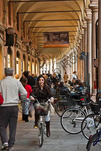 Modena: the porches in Emilia Centro Street with people walking and riding a bike.