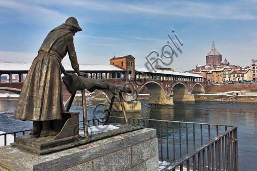 Pavia: the covered bridge on the Tessin river, built in 1949, according to the structure of the old covered bridge dating back at the XIV century. In the background, the Duomo (Cathedral) dome. In the foreground, bronze the monument dedicated to the river washerwoman.