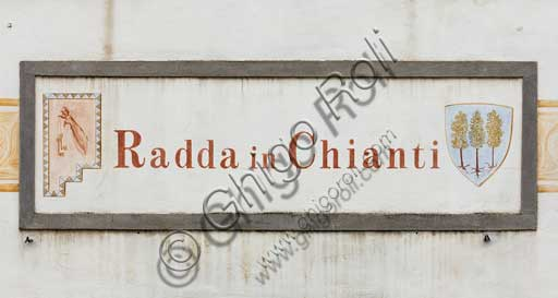 Radda in Chianti: sign with the name of the village on a facade.
