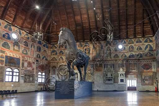"Padua, Palazzo della Ragione : the ""Salone"" (about 80 meters long and 27 meters wide)  is covered by a wooden structure almost 40 meters high. The wooden horse was donated to the City by the family Capodilista  in 1837. The horse had been made for a tournament in 1466. The frescoes were painted by John Miretto and by an unknown artist from Ferrara in the first half of the fifteenth century . The themes are the Zodiac, the trades of the year. There are also frescoes about religious themes."