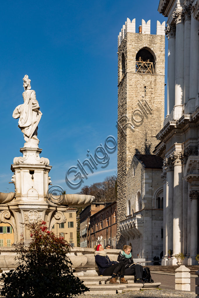 "Brescia, Paolo VI Square: view. From the left, the Broletto with the Pégol Tower and the Loggia delle Grida; and part of the facade of the Duomo Nuovo  (the New Cathedral) , in late Baroque style with the facade of Botticino marble. In the foreground, the fountain with a copy of the neoclassical statue of Minerva, known as ""Armed Brescia""."