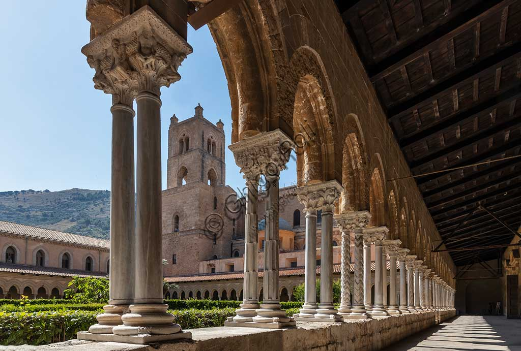 Monreale, Duomo, the cloister of the Benedectine monastery (XII century): series of twin columns and capitals on the Eastern side of the cloister. In the background, the bell tower of the Cathedral.